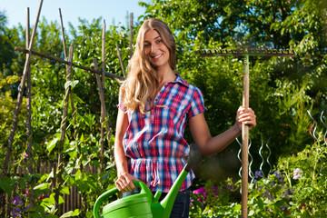 Gartenarbeit im Sommer - Frau mit Gießkanne und Rechen