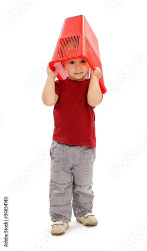 Little boy pulling garbage bin on head