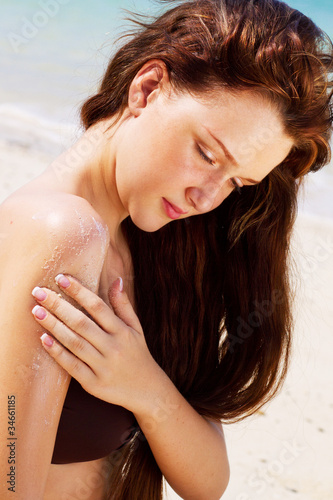 A young and attractive woman applying suntan lotion