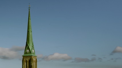 Timelapse clouds move past a green church steeple