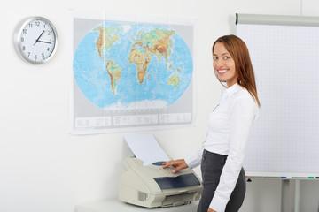 junge lächelnde geschäftsfrau am fax