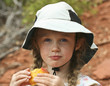 A Little Girl in a White Hat Eating a Peach