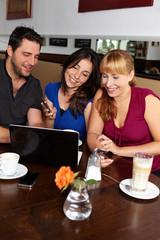 Gruppe mit Netbook und Handys im Café