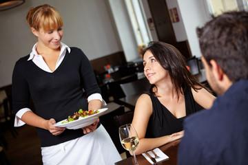 Kellnerin bringt Salat im Restaurant