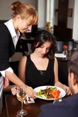 Kellnerin serviert einen Salat