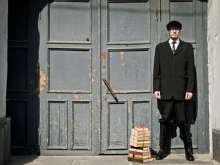 young man in vintage style is standing against the old door