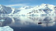 small boat travels through antarctic ocean