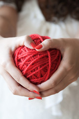 Big ball of red wool in the hands of a girl