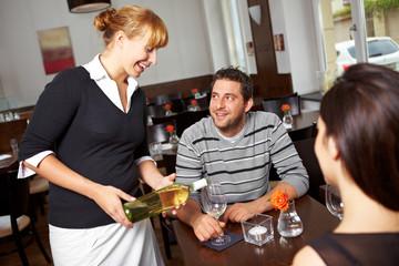 Kellnerin schenkt Weißwein ein