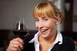 Lachende Frau prostet mit Rotwein