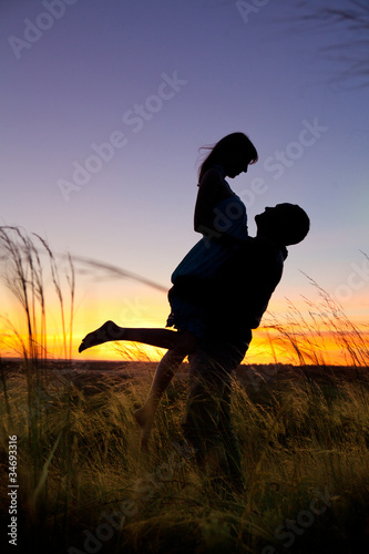 Couple on the sunset background.