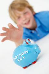 Young boy reaching for piggy bank