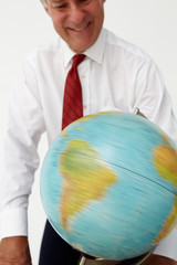 Senior businessman spinning globe