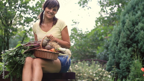 Young happy woman holding basket full of fresh vegetables