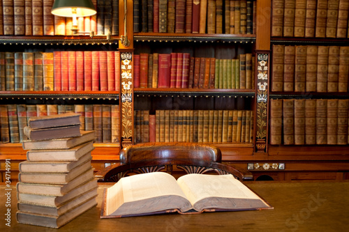 Old classic library with books on table - 34714991