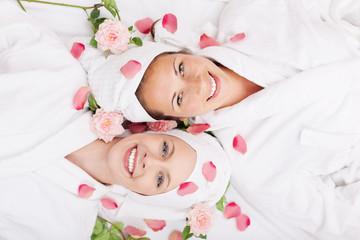 lachende freundinnen mit rosen im wellnessbereich