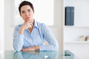 Thoughtful Businesswoman sitting behind a desk