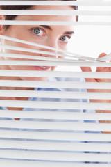 Beautiful brunette businesswoman peeking through a venetian blin