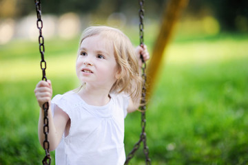 Adorable little girl having fun on a swing