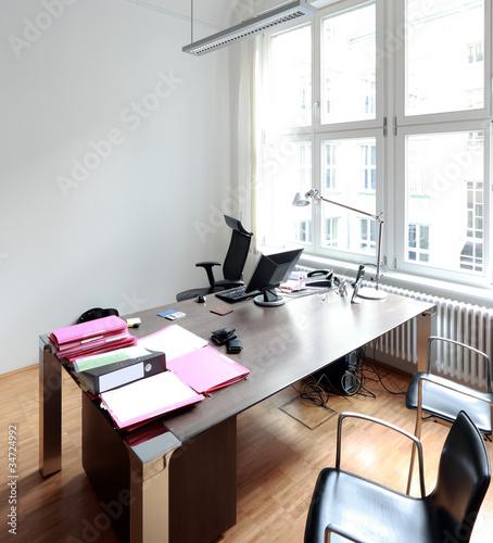 Aufgeräumter Schreibtisch mit weisser Wand im Büro