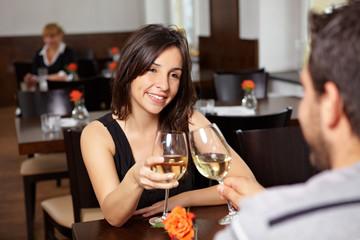 Paar im Restaurant prostet sich zu