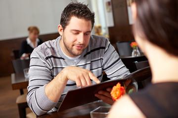 Mann wählt Menu aus Speisekarte in Restaurant