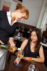 Kellnerin gießt Frau Wein ein
