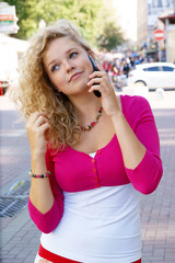 Young blonde woman with mobile phone in the street