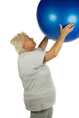 Senior woman with a fit ball on white background