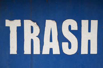A Grungy, Weathered Trash Sign On A Blue Background