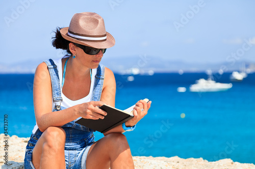 Young woman reading a book on the beach.