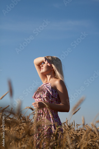 The beautiful girl in the field with wheat