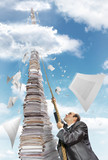 Businessman climbing up the pile of paperwork