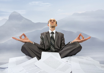 Businessman meditating in mountains