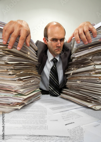 Businessman with big piles of paperwork