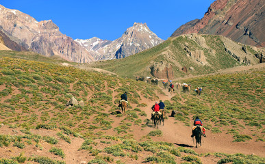 Mountain valley with hikers on horses as seen in Argentina