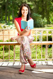smiling girl with book in park