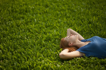 girl lying on the grass and sleeping peacefully