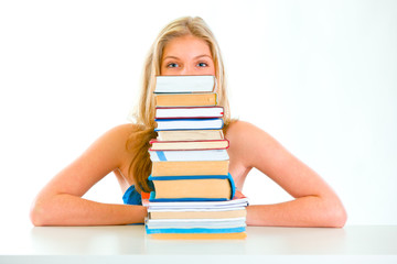 Sitting at table teen girl looking out of pile of book