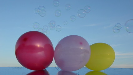 three balloons on mirror and soap bubbles