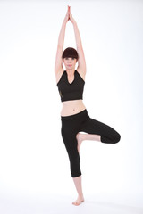 Beautiful fit woman in Yoga Tree Pose Vrksasana