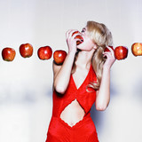 Young pretty woman in a fashionable dress with apples