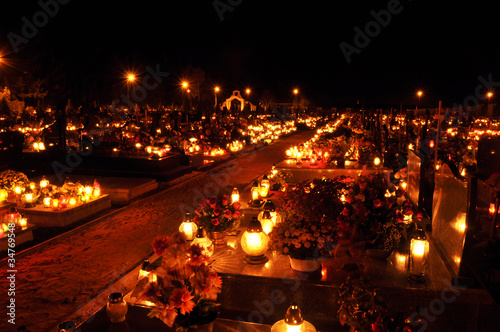 Leinwanddruck Bild Candle flames illuminating on cemetery during All Saint's Day