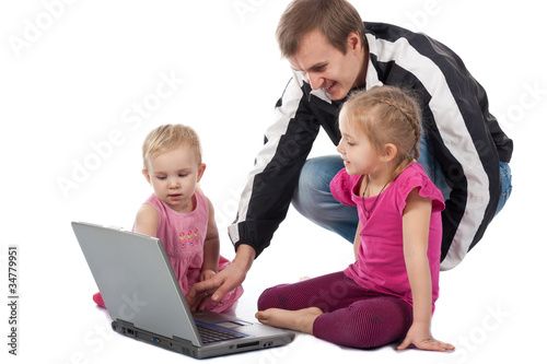 Father with children playing computer games on laptop