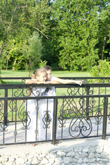 little girl talks to the friend on the bridge