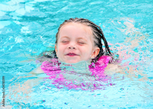 Young child swimming in pool with lifejacket