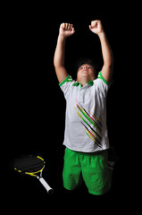 Tennis boy celebrating isolated in black