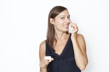 Atrraktive Frau trägt Creme auf ihr Gesicht auf