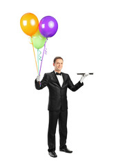 Butler holding an empty tray and balloons
