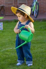 little baby boy gardener watering the grass